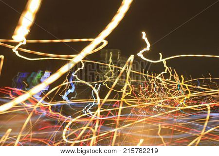 Abstract Light Trail Lines Background. Irregular Pattern, Blurred Festive Christmas Decoration Wallpaper. Multicolored Yellow, Gold, White and Red and Blue Vibrant Colors, City Outdoor Ornament.