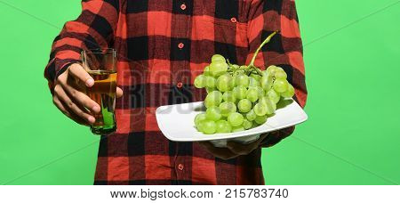 Guy Shows Harvest. Male Hands Hold Glass Of Grape Juice