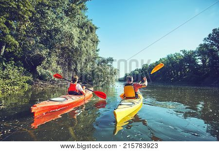 Man paddling in a kayak on river.