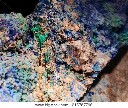 Colorful closeup photograph of malachite and azurite minerals. With small part of black background. Natural phenomenon. Abstract look. Green, blue, indigo, brown colors.