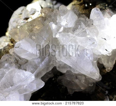 Closeup photograph of calcite with pyrite. Transparent, glittering, with small part of black background. Natural phenomenon. Abstract look.