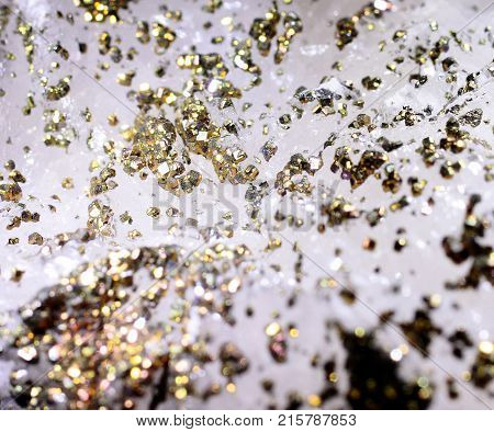 Closeup photograph of epitaxy of pyrite on calcite. Golden details. Natural phenomenon. Very abstract look.