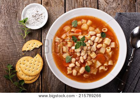 Vegetarian minestrone soup with pasta and white beans overhead view
