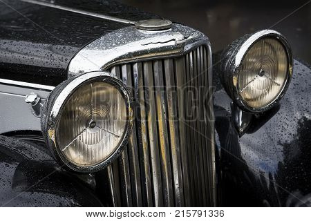 MOSCOW, RUSSIA - AUGUST 26, 2017: Close-up of Jaguar car detal, hood with headlights on a vintage car. Retro cars festival. Rainy evening, real dark background