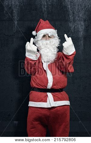 bad santa claus showing middle finger in front of grunge wall