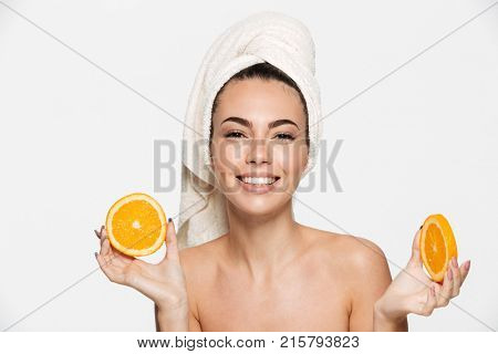 Close up beauty portrait of an excited attractive half naked woman with a towel wrapped around her face holding orange slices at her face and looking at camera isolated over white background