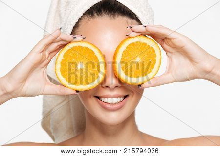 Close up beauty portrait of a cheerful attractive half naked woman with a towel wrapped around her face holding orange slices at her face and looking at camera isolated over white background