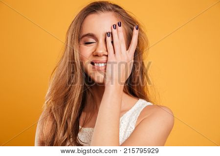 Close up portrait of a pretty smiling girl laughing with eyes closed isolated over yellow background