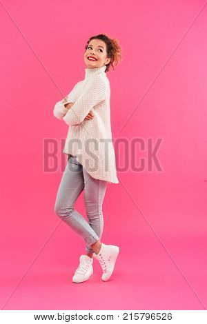 Full length portrait of an attractive smiling girl posing while standing and looking away isolated over pink background