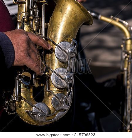 Playing the sax in the Retiro Park in the city of Madrid. Spain