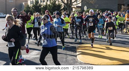 West Islip NY USA - 24 November 2017: The middle of the pack of a group of runners racing a local turkey trot on Thanksgiving weekend.