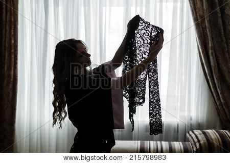 young woman dressed in a robe holds and consider a lacy transparent underwear silhouette in a backlight on a window background