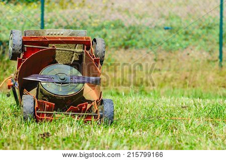 Gardening. Broken old lawnmower in backyard grass.