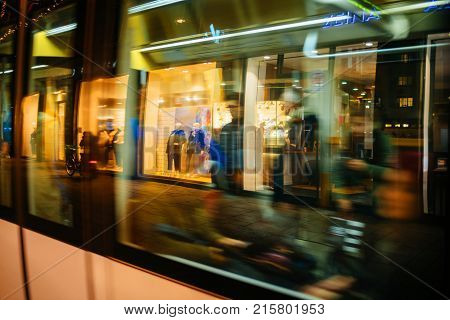 STRASBOURG FRANCE - NOV 21 2017: Shop displays and Christmas light decorations reflected in tramway passing by at night in Strasbourg