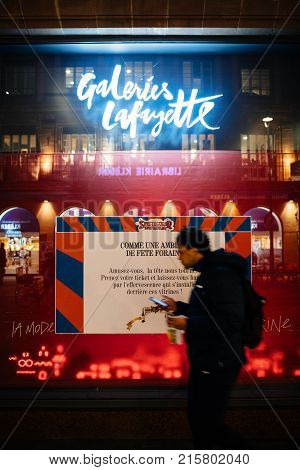 STRASBOURG FRANCE - NOV 21 2017: Man checking phone and eating while passing by Galeries Lafayette shop display in preparation for Christmas decoration