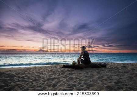 Pensive young man with coconut drink relaxing on the beach during beautiful sunset.