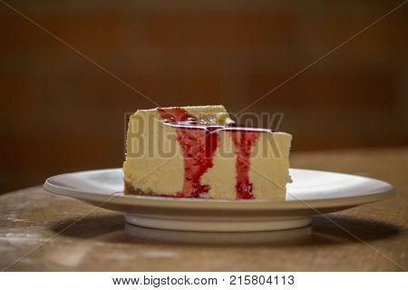Delicious slice of cheesecake topped with raspberry sauce