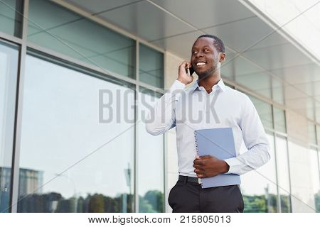 Happy black businessman with smartphone and notepad outdoors. Young african-american salesman working with mobile and papers, standing in urban area cityscape
