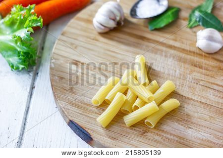 Rigatoni pasta over the wooden kitchen board.