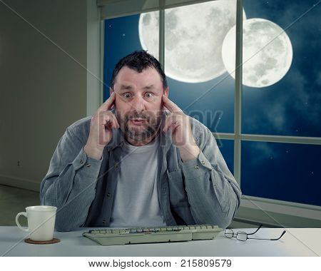 Man with bulging eyeballs is frightened to turn around to look again at two moons on night sky in the window. Scared middle-aged man holds his head with fingers. Man has never seen double moon
