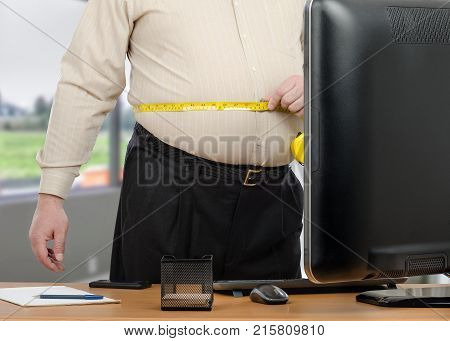 Businessman calculates distance around his waist with tape meter in front of big monitor in the office during virtual nutritionist appointment