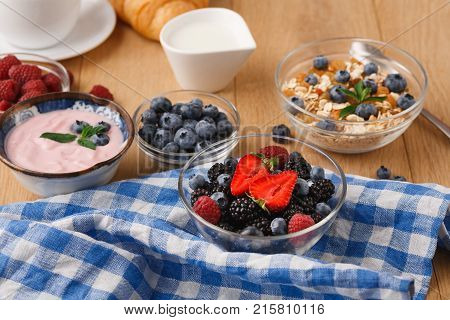 Tasty breakfast with light greek yogurt, muesli, fresh strawberries, raspberries, blueberries and blackberries. Low fat morning meals and healthy start of the day. Detox and diet concept