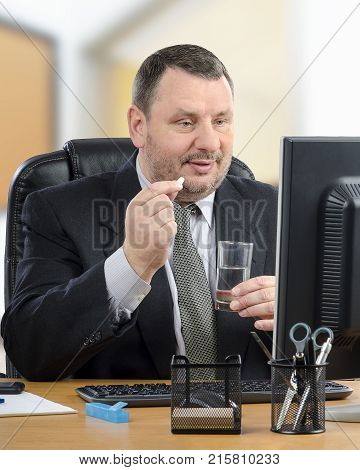 Manager intends to swallow white pill during telehealth doctor appointment. Mature man in black suit sits at his office desk looking to computer monitor