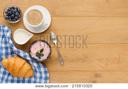 Rich continental breakfast background. French crusty croissants, greek yogurt, lots of sweet berries and hot coffee for tasty morning meals. Delicious start of the day. Top view, copy space wood