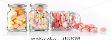 colorful candies in glass jars on white background - Web banner with food concept