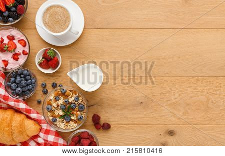 Tasty breakfast with light greek yogurt, muesli, fresh organic berries and black coffee. Low fat morning meals and healthy start of the day. Detox and diet concept, top view, copy space