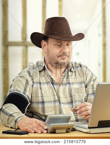 Cowboy makes self-monitoring of blood pressure with telehealth support. Middle aged farmer wearing plaid shirt and brown hat sits in front of computer. Man suffers hypertension measures BP levels at regular intervals and transmit it to telemedicine headqu