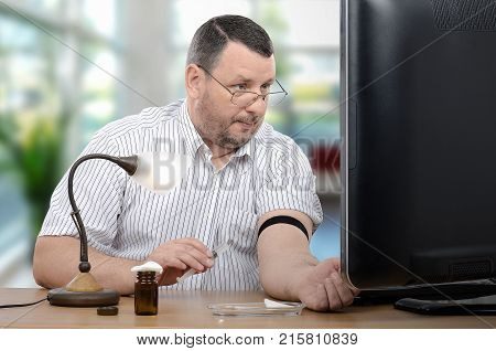 Manager looks at big computer monitor holding syringe in hand. Businessman starts to take an intravenous injection alone. Telemedicine service helps middle aged man with it