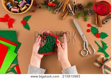 Making handmade craft christmas ornaments, knitted Christmas stocking. Woman's leisure, holiday decorations. Top view of table with female hands and trappings. Creative diy craft hobby.