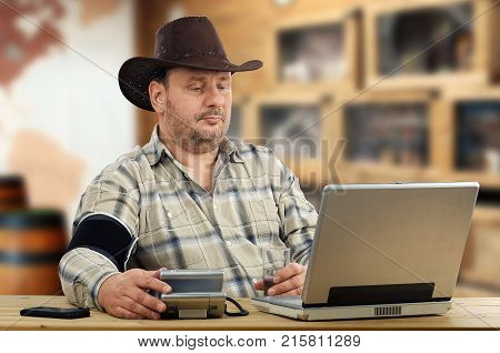 Remote ranch owner learns monitoring blood pressure on regular base with help of telemedicine service. Middle aged cowboy sits in front of computer. He measures BP for sending outcomes to virtual doctor
