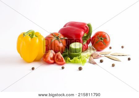 Red peppers and yellow peppers with tomatoes on a white background. Fresh vegetables on a white background. Composition from vegetables. Red and yellow peppers on a white background. Tomato with peppers and cucumber on a white background.