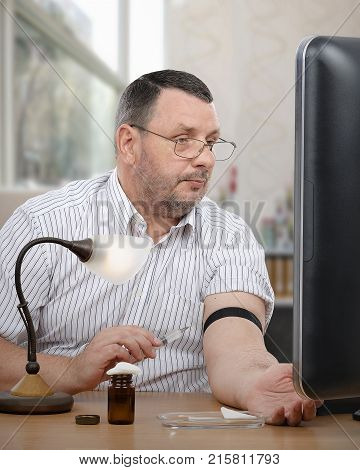 Businessman in white striped shirt looks at computer monitor with syringe in hand. Middle-aged man tries to do an intravenous injection alone either telehealth control or watching video course online