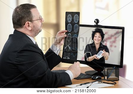 Virtual male doctor uses videoconferencing to communicate with remote patient. Man goes over brain x-rays image in front of woman in computer monitor. Optimistic mature woman has just measured blood pressure and shows outcomes
