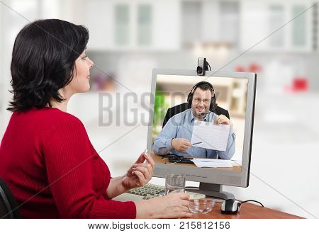 Woman in red jumper takes pills during virtual appointment with cardiologist. Friendly doctor points out the positive dynamics in her heart-rate graph. He is seen in computer monitor on the desk