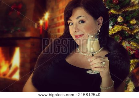 Mature woman wearing black fur holds cocktail glass with cream liqueur looking at the camera. Mid-shot on Christmas tree blurred background