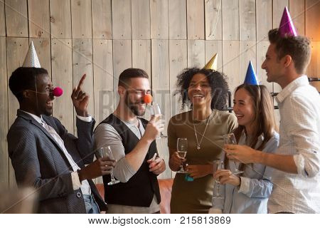 Multiracial young friends celebrating indoors, diverse happy people holding glasses drinking champagne and having fun at party, happy african and caucasian group joking laughing together