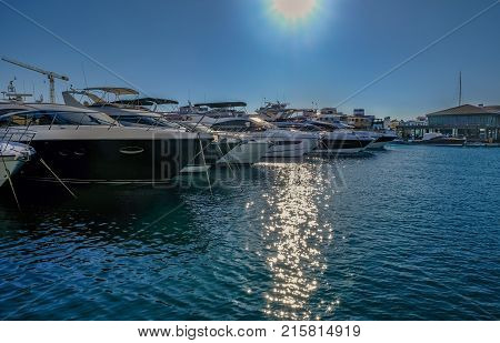 Row of luxurious motorboats in Limassol Marina. Morning shot on a bright blue sky day.