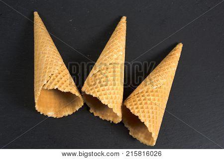 three empty ice cream waffers on black background