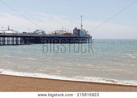 BRIGHTON GREAT BRITAIN - JUN 15 2017: Brighton pier green sea and the pebble beach. June 15 2017 in Brighton Great Britain
