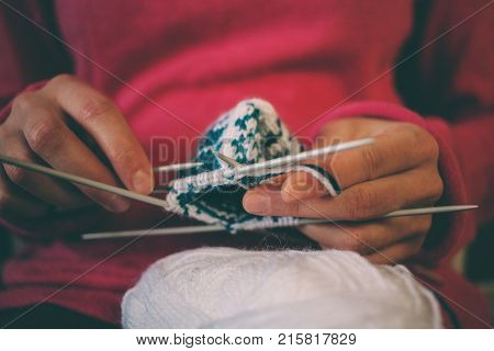 The woman knits knitting. Female hands hold the skein of thread and knitting needles. Fingers knitters. Mittens with jacquard pattern.