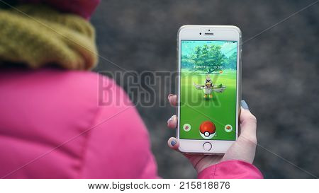 Samara, Russia - November 28, 2017: woman playing pokemon go on his iphone. pokemon go multiplayer game with elements of augmented reality.