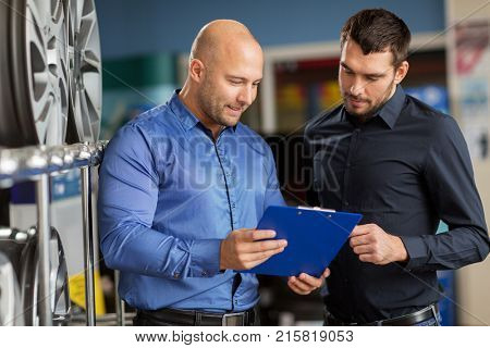 business, maintenance and people concept - male customer choosing alloy wheel rims and salesman with clipboard at car repair service or auto store