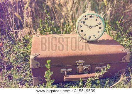 Vintage alarm clock on an old classic brown leather suitcase on a background of green grass. Retro toning. Travel concept