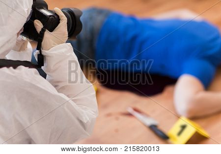 murder, investigation and forensic examination concept - criminalist with camera photographing dead male victim body at crime scene (staged photo)