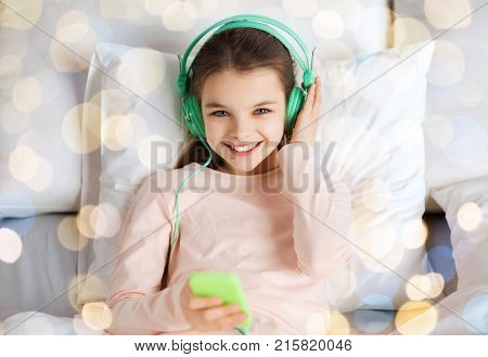 people, children and technology concept - happy smiling girl lying awake with smartphone and headphones in bed listening to music over holidays lights background