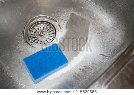 Cleaning kitchen sink. How to clean the stainless steel sink with cleanser and washcloth. Blue sponge and scouring powder against the background of a metal sink